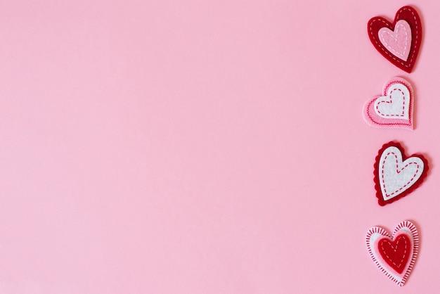 De achtergrond van valentijnsdag. grens van mooie verschillende harten op een roze achtergrond