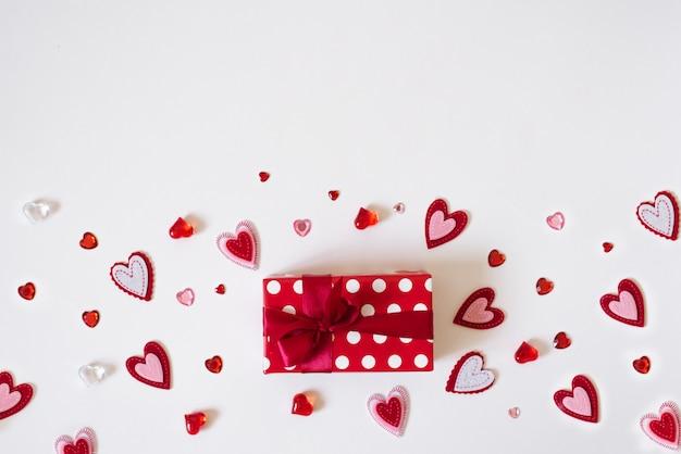 De achtergrond van valentijnsdag. rode geschenkdoos met rood satijnen lint en veel verschillende harten