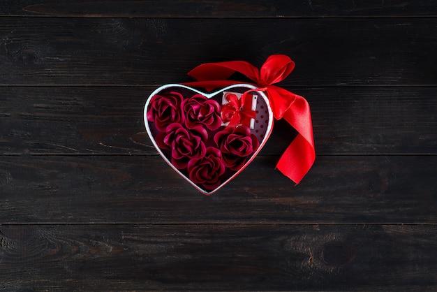 De achtergrond van valentijnskaarten met minigift en nam in hartdoos toe