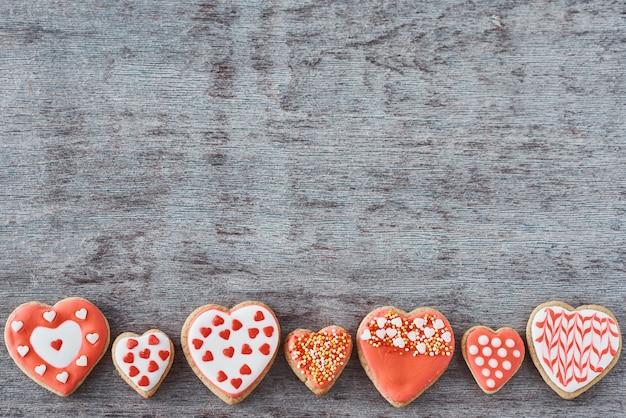 De achtergrond van verfraaid met suikerglazuur en de verglaasde koekjes van de hartvorm op grijze vlakke achtergrond, lag. valentijnsdag eten concept