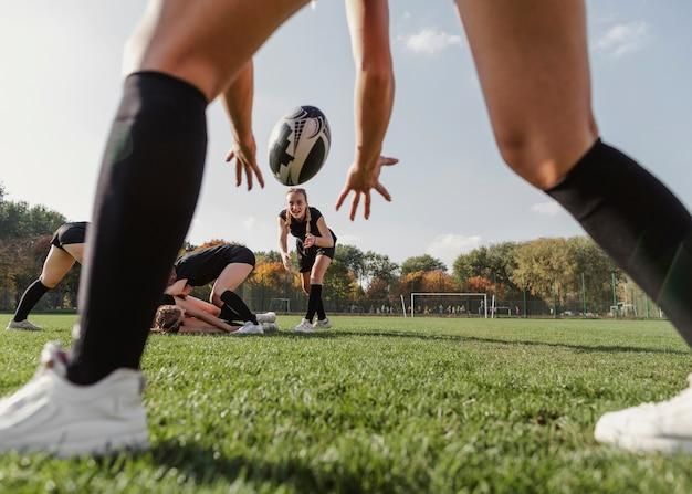 De achterhanden van meningsvrouwen die een rugbybal proberen te vangen