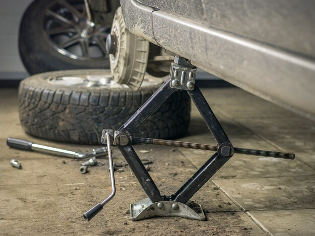 De achterkant van de auto in de garage met het verwijderde wiel.