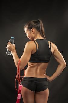 De achterkant van de gespierde jonge vrouw atleet met een springtouw drinkwater op zwarte achtergrond.