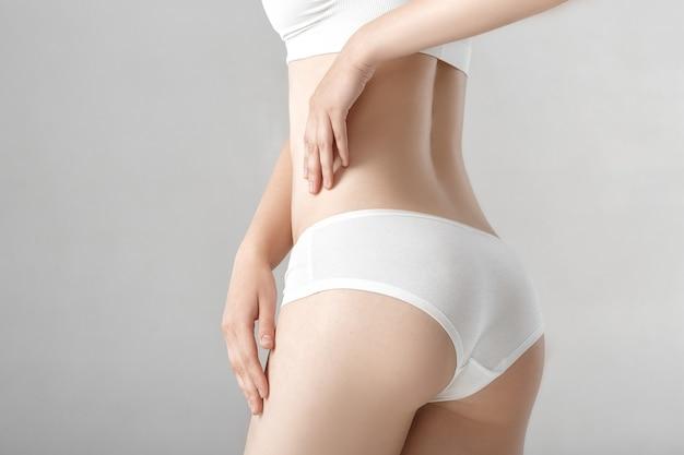 De achterkant van de vrouw in witte lingerie op de grijze