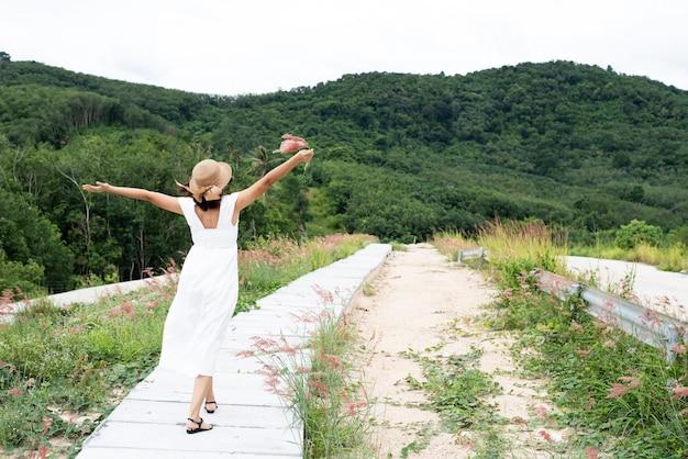 De achterkant van de vrouw lopen op cement begane grond, met ontspannen gevoel, zijaanzicht van het land