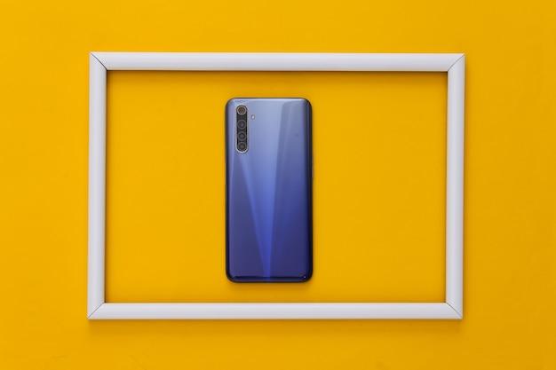 De achterkant van een moderne smartphone met lenzen op geel met wit frame