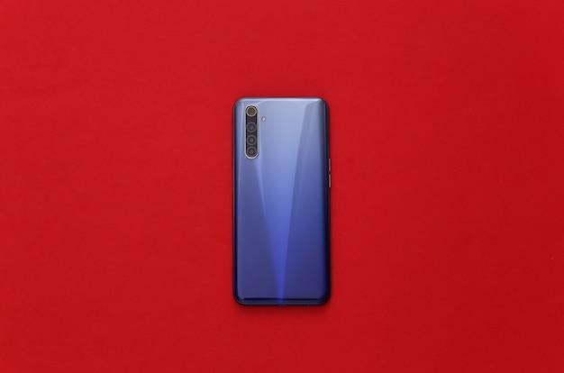 De achterkant van een moderne smartphone met lenzen op rood met wit frame