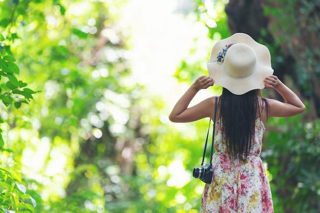 De achterkant van het geluk meisje met een strooien hoed in de tuin