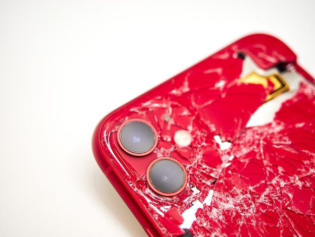 De achterkant van moderne rode smartphone met een gebroken glas en een beschadigd gebogen lichaam close-up geïsoleerd op een wit oppervlak