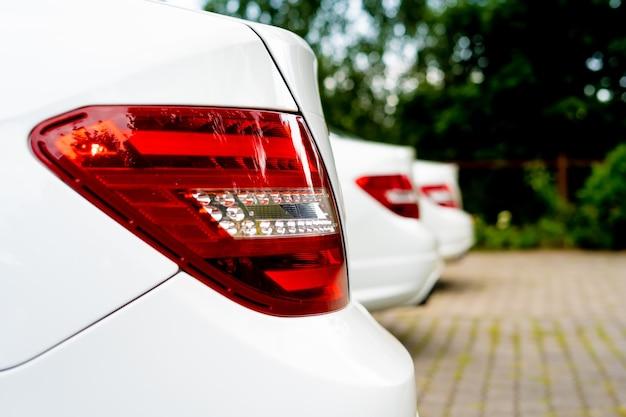 De achterkant van witte auto's die op een rij staan.