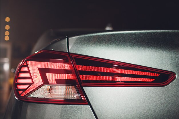 De achterlichten van een moderne prestigieuze auto vanuit een nauwe hoek, de autoshow.