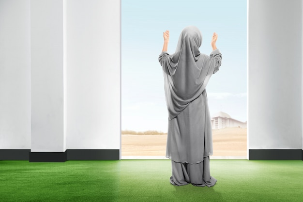 De achtermening van aziatisch meisje in sluier die zich op tapijt bevinden heft de hand op en starend de hemel van binnenuit de ruimte