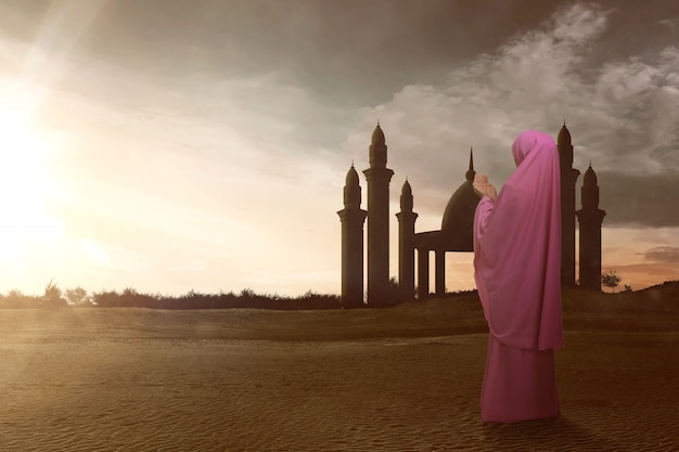 De achtermening van aziatische moslimvrouw met sluier bidt aan god