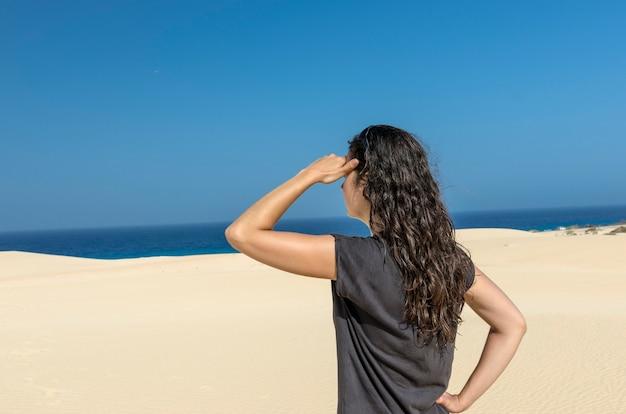 De achtermening van donkerbruine vrouw met haar dient haar voorhoofd in kijkend aan overzees.