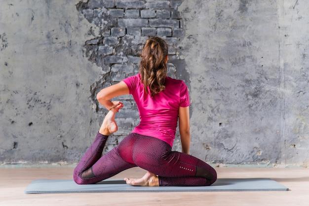 De achtermening van een jonge vrouw die yoga doet stelt voor grijze muur