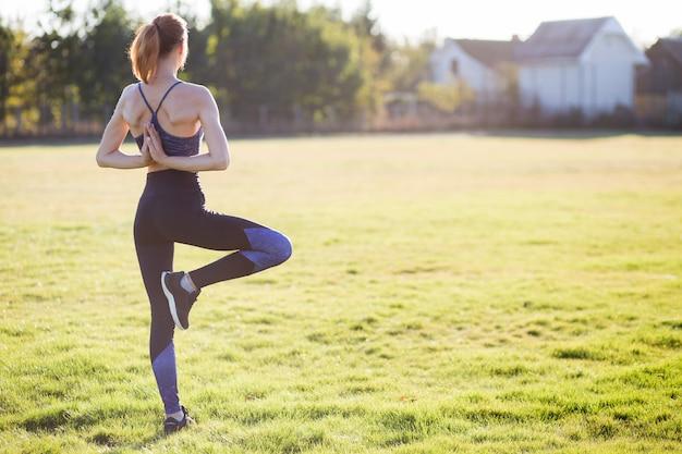 De achtermening van jong meisje in yogapositie mediteert op gebied bij zonsopgang