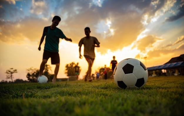 De actiesport van het silhouet in openlucht van een groep jonge geitjes die voetbal van het pret de speel voetbal voor oefening hebben