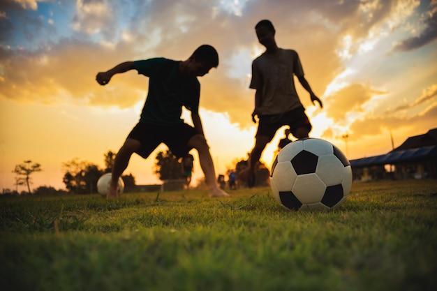 De actiesport van het silhouet in openlucht van een groep jonge geitjes die voetbal van het pret de speel voetbal voor oefening hebben.