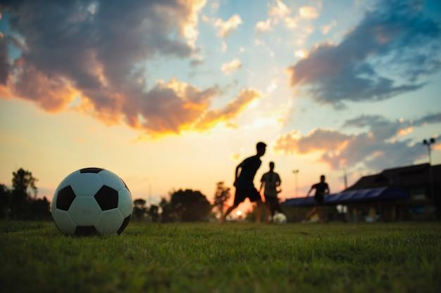 De actiesport van het silhouet in openlucht van een groep jonge geitjes die voetbal van het pret speelvoetbal hebben