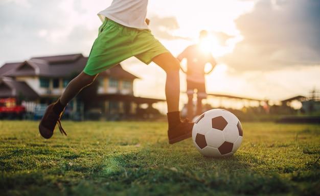 De actiesport van het silhouet in openlucht van een groep jonge geitjes die voetbalvoetbal spelen.