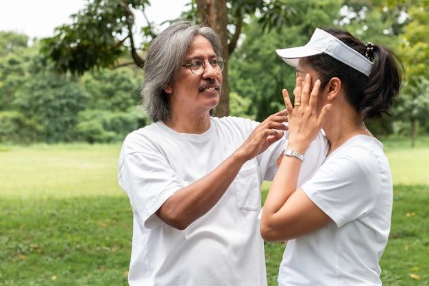 De actieve aziatische paaroudste in sportkleding veegt zweet af na het uitoefenen in het park.
