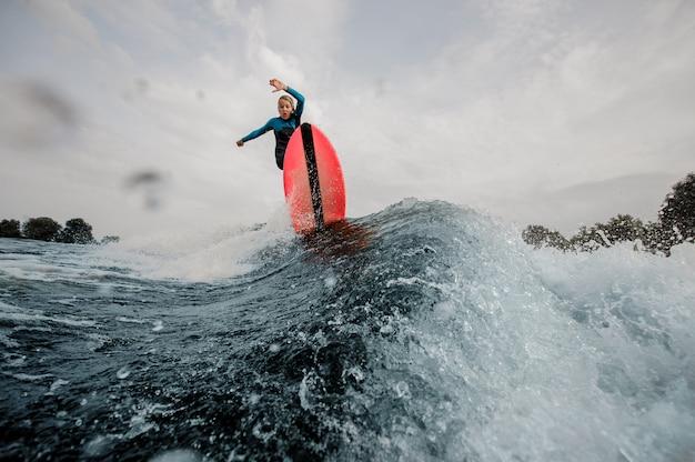 De actieve kindjongen kleedde zich in zwempak surfen die op oranje raad springen