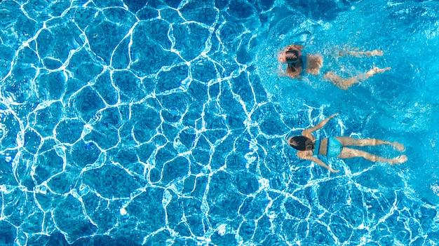 De actieve meisjes in lucht de hommelmening van het zwembadwater van hierboven, kinderen zwemmen, de jonge geitjes hebben pret op tropische familievakantie, het concept van de vakantietoevlucht