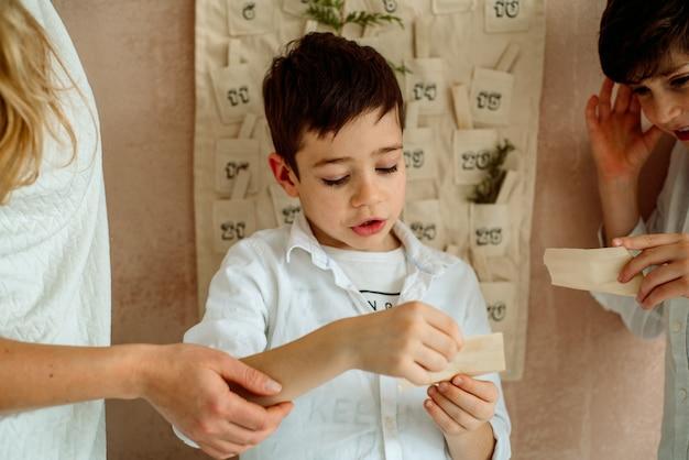 De adventskalender die aan de muur hangt. cadeaus verrassingen voor kinderen. twee emotionele jongens
