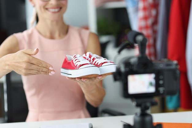 De adviseur van de vrouwenverkoper toont aan camera rode sportschoenen. kinderen keuze van sportschoenen concept