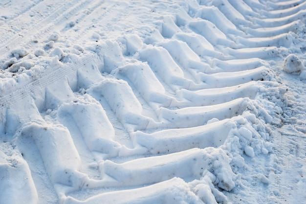 De afdruk van het loopvlak van de tractorwielen in de sneeuw.