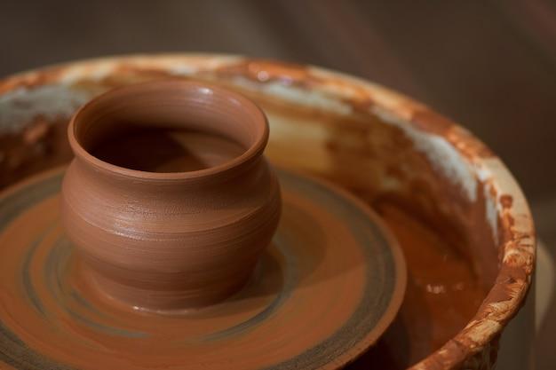 De afgewerkte aarden pot staat op een pottenbakkerswiel