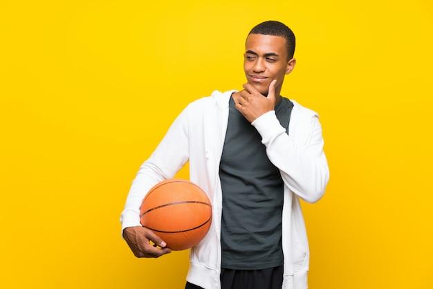 De afrikaanse amerikaanse mens die van de basketbalspeler een idee denkt