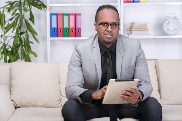 De afrikaanse amerikaanse mens gebruikt thuis digitale tablet.