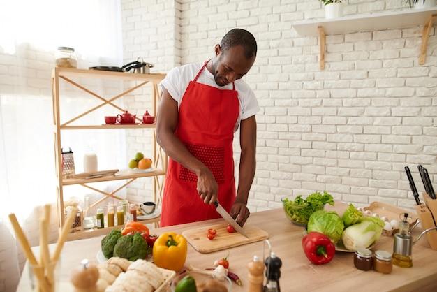 De afrikaanse amerikaanse mens in schort snijdt tomaten in keuken
