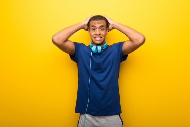 De afrikaanse amerikaanse mens met blauwe t-shirt op gele achtergrond neemt handen op hoofd omdat heeft migraine