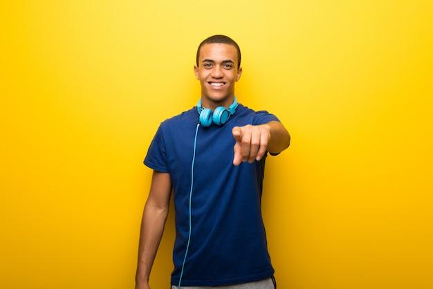 De afrikaanse amerikaanse mens met blauwe t-shirt op gele achtergrond richt vinger op u met