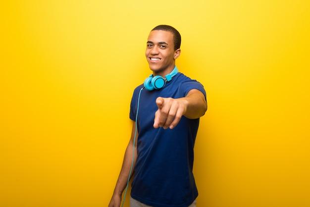 De afrikaanse amerikaanse mens met blauwe t-shirt op gele achtergrond richt vinger op u