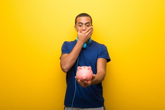 De afrikaanse amerikaanse mens met blauwe t-shirt op gele achtergrond verraste terwijl het houden van een grote piggybank