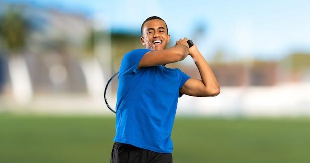 De afrikaanse amerikaanse mens van de tennisspeler bij in openlucht