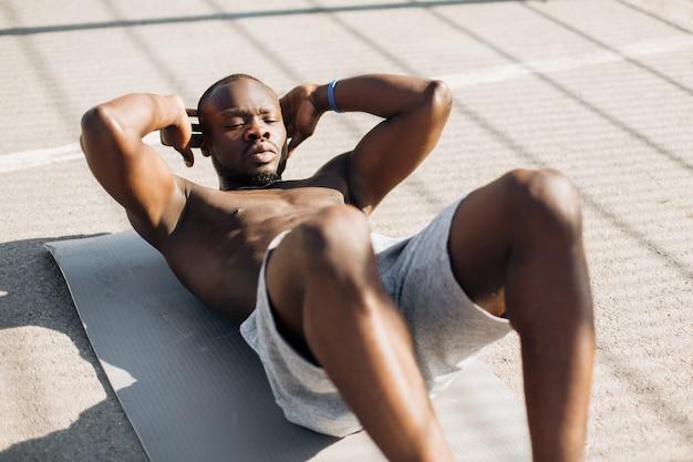 De afrikaanse amerikaanse mens werkt zijn abs uit die op de grond buiten ligt