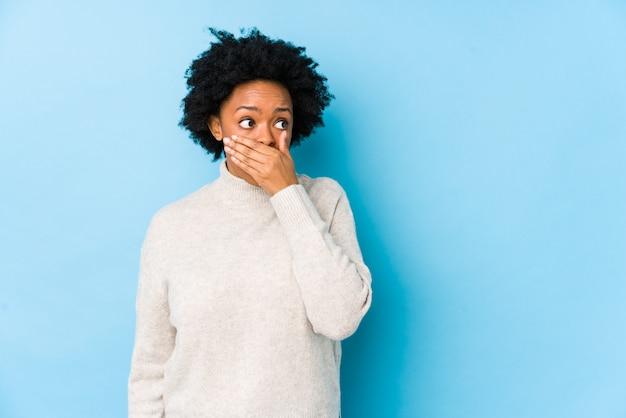 De afrikaanse amerikaanse vrouw van middelbare leeftijd tegen een blauwe achtergrond isoleerde het nadenkende kijken aan een exemplaarruimte die mond behandelen met hand.
