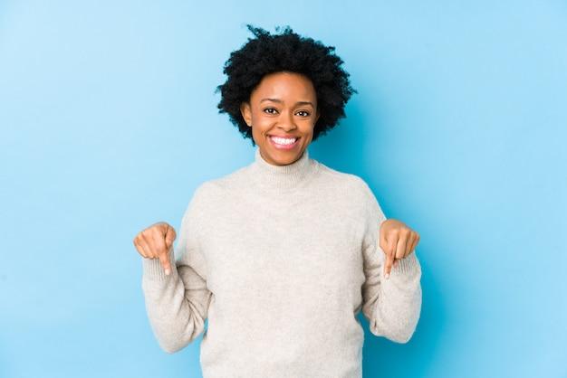 De afrikaanse amerikaanse vrouw van middelbare leeftijd tegen een blauwe geïsoleerde muur wijst neer met vingers, positief gevoel.