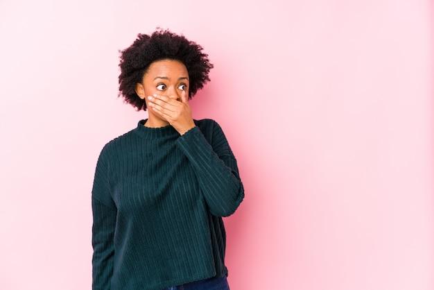 De afrikaanse amerikaanse vrouw van middelbare leeftijd tegen een roze achtergrond isoleerde het nadenkende kijken aan een exemplaarruimte die mond behandelen met hand.