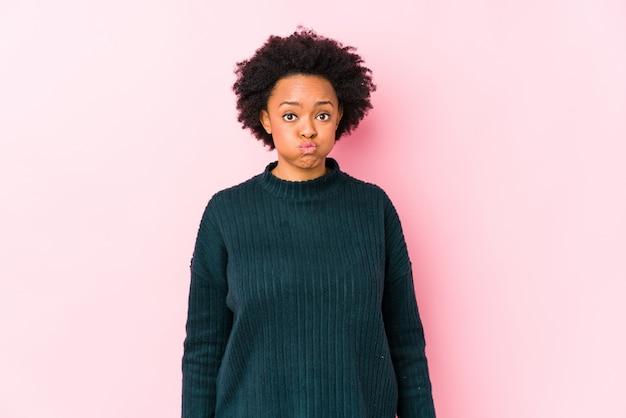De afrikaanse amerikaanse vrouw van middelbare leeftijd tegen een roze geïsoleerde muur blaast wangen, heeft uitdrukking vermoeid. gelaatsuitdrukking concept.