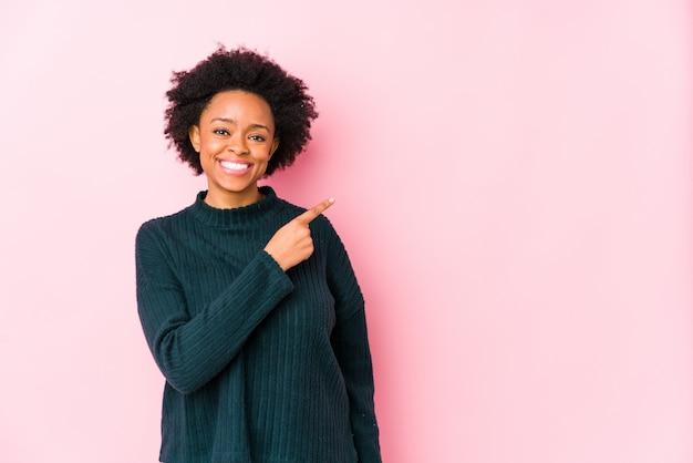 De afrikaanse amerikaanse vrouw van middelbare leeftijd tegen een roze muur isoleerde opzij glimlachend en richtend, tonend iets op lege ruimte.