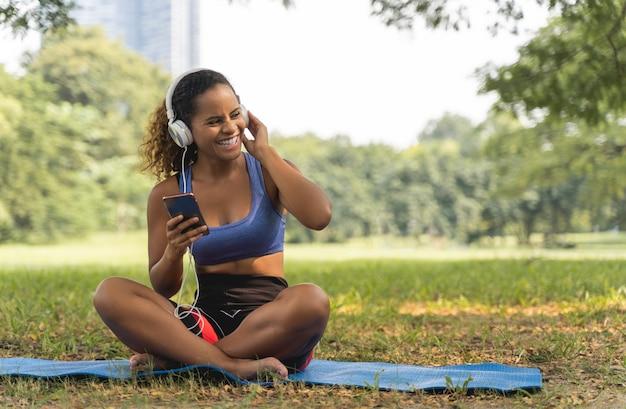 De afrikaanse amerikaanse vrouwen die en aan de muziek in het park zitten luisteren voor ontspannen levensstijl