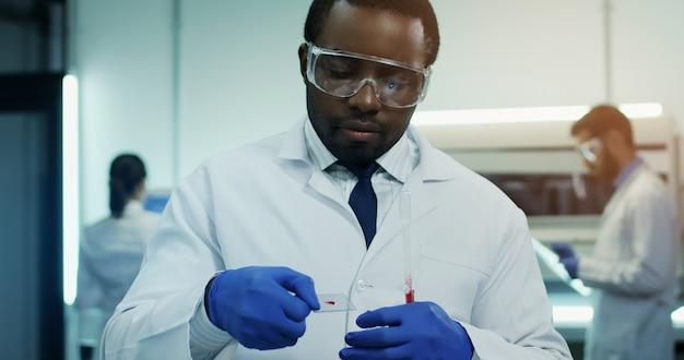 De afrikaanse amerikaanse wetenschapper die van het jonge mensenlaboratorium een bloedonderzoek met een buis in handen maken. portret.