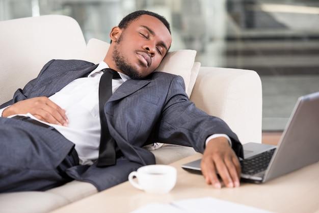 De afrikaanse bedrijfsmens houdt hand op laptop