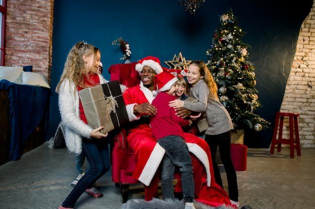 De afrikaanse kerstman zit op de achtergrond van de kerstboom en presenteert geschenken aan de kinderen