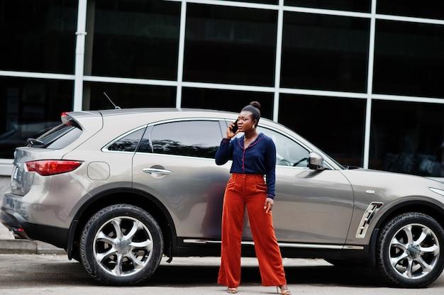 De afrikaanse vrouw in oranje broek en blauw overhemd stelde tegen zilveren suv auto en spreekt op mobiele telefoon.